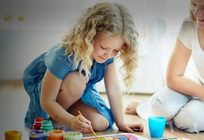 photo of woman watching over a child coloring using paints